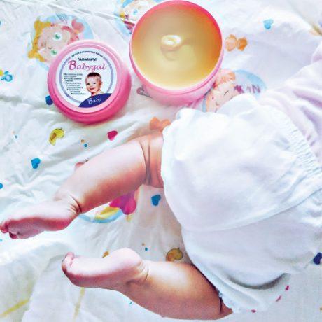 beba koja puzi pored otvorene kremice za negu bebe i decu